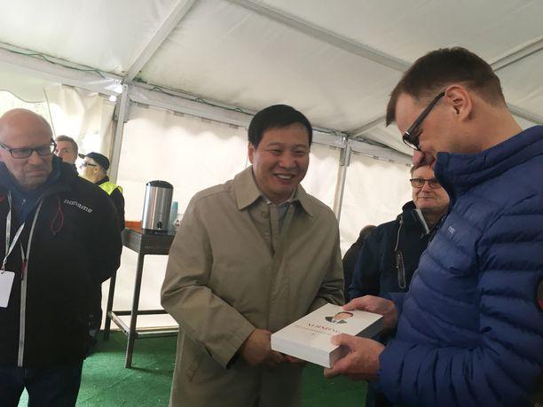 Pääministeri Juha Sipilää hymyilytti, kun hän sai kiinalaisdelegaatiolta lahjaksi Xi Jinping -teoksen.