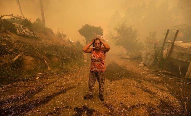 Metsäpalosta selviytynyt nainen kulki järkyttyneenä raunioiden keskellä.