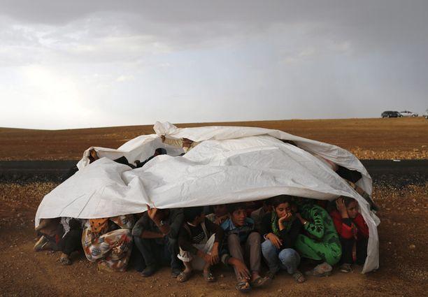 Taisteluja paenneet pakolaiset suojautuivat sateelta.