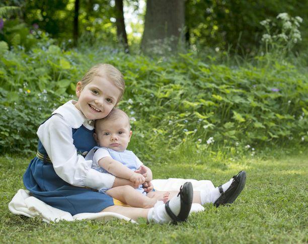 Prinsessa Estelle pukeutui kansallispukuun Ruotsin kansallispäivän kunniaksi. Sylissä kameraan tuijottaa pikkuveli, keväällä syntynyt prinssi Oscar.