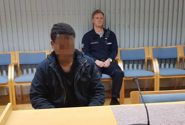 Mies istui syytetyn penkille, eikä peitellyt kasvojaan istunnon aluksi.
