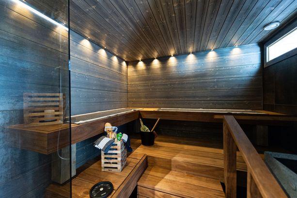 Pihasauna on väritykseltään tumma. Hämyinen tunnelma sopii pihasaunan konseptiin. Takkaa lämmitetään viereiseen huoneeseen aukeavan luukun kautta.