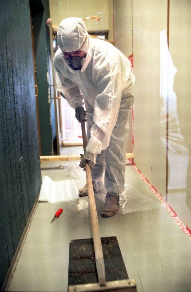 Asbestia sisältävän rakenteen saa uuden lainsäädännön mukaan purkaa vain siihen koulutuksen saanut työntekijä. Suojavarusteet ovat välttämättömät. Kuvassa avataan tamperelaisen virastotalon lattiaa.