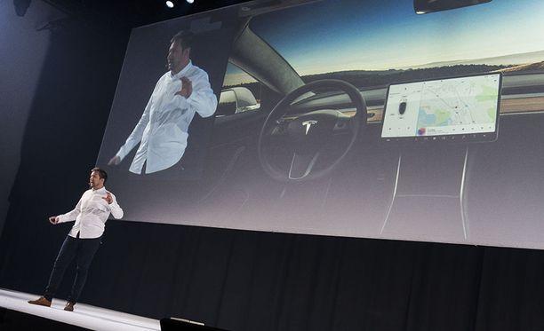 Teslan muotoiluosastolla aiemmin työskennellyt Joonas Vartola havainnollistaa sisätilojen uutta tyylisuuntaa Tesla Model 3:n ohjaamolla. Painikkeita on vain 14 kappaletta.