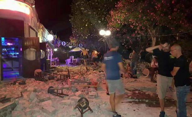 Turisteja baarin ulkopuolella maanjäristyksen jälkeen. Taustalla näkyy maassa makaava mies.