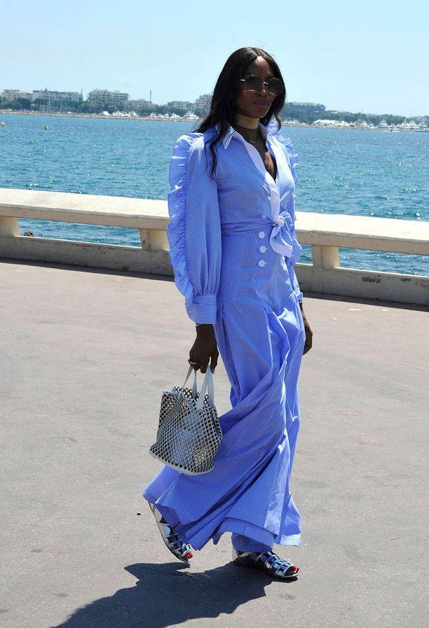Mallilegenda Naomi Campbell edusti Cannesissa asussa, joka sopii miljööseen täydellisesti. Kesäisen kevyt raitahaalari saa täydellisen parin trendikkäästä verkkolaukusta ja hopeisista sandaaleista.