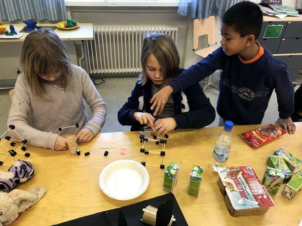 Lumi (vasemmalla) ja Jack rakentelivat lakupaloista ja hammastikuista kiipelytelineiden pienoismalleja. Julius antoi neuvoja.