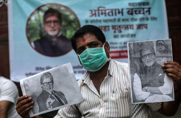 Bollywood-tähti Amitabh Bachchanin fani kannattelee häntä esittäviä kuvia ja toivottaa samalla pikaista paranemista Intian kuuluisammalle COVID-19-potilaalle.