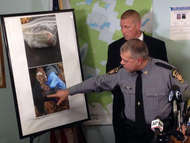 Everstiluutnantti George Bivens esittelee metsästä löytynyttä putkipommia.