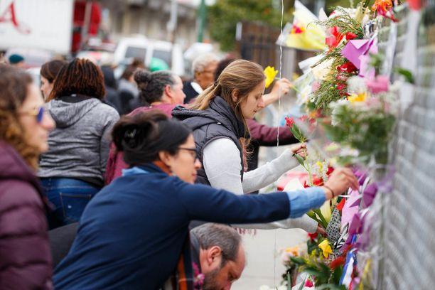 Ihmiset kerääntyivät joulukuun alussa palaneen rakennuksen lähistölle muistamaan tulipalon uhreja.
