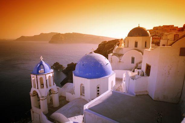 Santorinin kirkkojen siniset katot ovat maalauksellinen näky auringonlaskun aikaan.