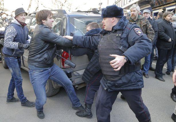 Mielenosoittajat yrittivät estää poliisia viemästä Navalnyitä autolla pois.