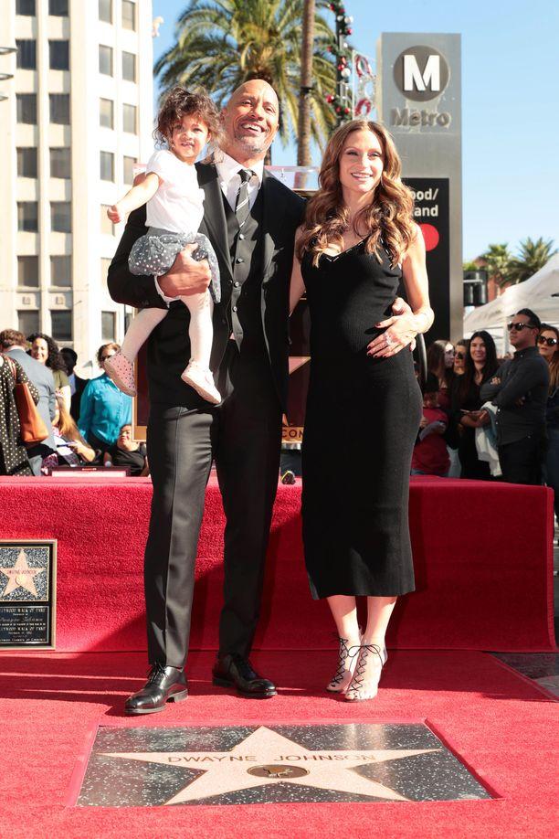 Dwayne Johnson poseeraa Lauren Hashianin ja heidän Jasmine-tyttärensä kanssa näyttelijän Walk of Fame -tähden edustalla.