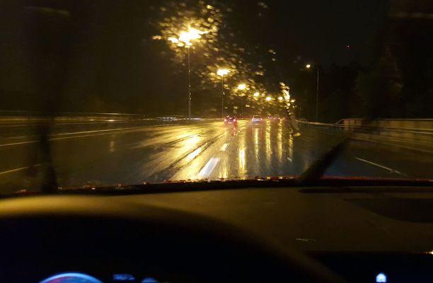 Vesi kiiltää asvaltissa ja velloo tuulilasissa. Kuljettajan on syytä hidastaa auton vauhtia.