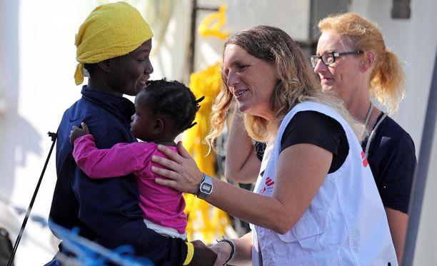 Punaisen ristin työntekijä ottamassa pakolaisia vastaan Sisilian Palermossa perjantaina 13. lokakuuta.