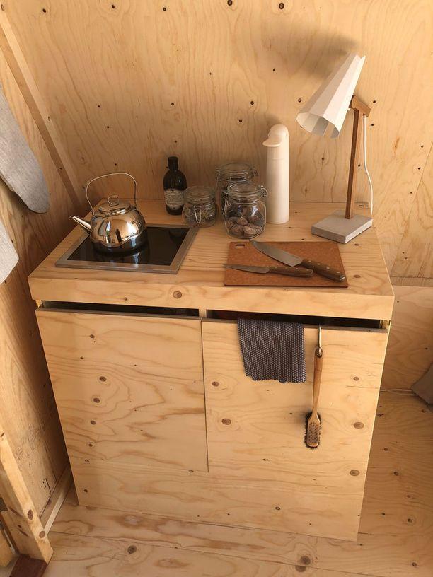 Kätevä keittonurkkaus sopii paitsi ruuanlaittoon, myös lämmittää mökin viileämpinä kesäöinä.