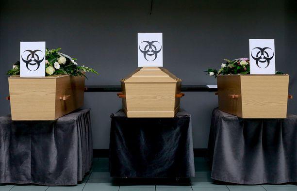 Koronaan kuolleiden arkut on merkitty ympäristövaaraa ilmaisevin merkein Belgiassa.