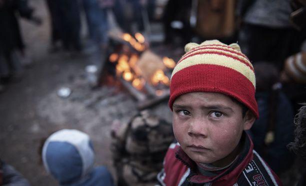 Lapsi lämmittelee nuotion edessä paettuaan Isisin ja Irakin joukkojen taistelua Mosulin lähellä maaliskuussa 2017.