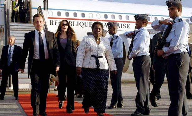 Carla Bruni asteli punaista mattoa pitkin Cape Townin lentokentällä Etelä-Afrikassa, jossa vastaanottajana oli maan ulkoministeri Nkosazana Dlamini Zuma.