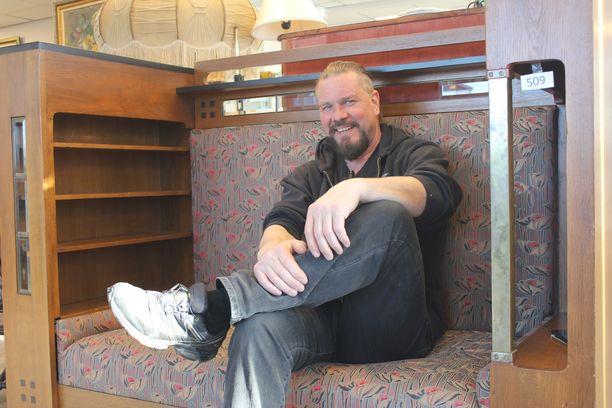 Martti Ekman istuu Eliel Saarisen 1900-luvun alkupuolella suunnittelemalla sohvalla. Huonekalu vaihtoi omistajaa useilla tuhansilla euroilla.