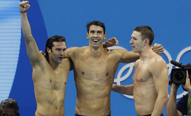 Michael Phelps iloitsi joukkuetovereidensa keskellä.