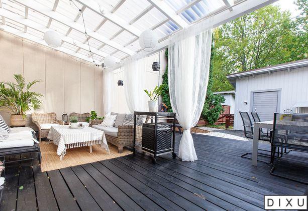 Valokate tarjoaa suojaa tälle terassille. Ruokailuryhmän lisäksi katteen alla sijaitsee olohuonemainen kulmaus. Kulmaus on sisustettu olohuonemaiseksi maton, pehmeiden tekstiilien, viherkasvien ja verhojen avulla. Kattoon ripustetut lyhdyt ja valot näyttävät kauniilta illan hämärtyessä.