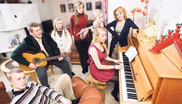"""""""Tulkaa kaikki nyt laulamaan..."""" Räsäsillä lauletaan joululauluja. Vas. Sakari, Niilo soittaa kitaraa, Juulia, Mirjami, Esteri soittaa poikki-huilua ja Saara säestää pianolla, Päivi takana."""