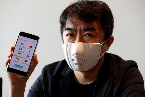 Toimitusjohtaja Taisuke Ono esittelee kieliä kääntävää kasvomaskia ja siihen liittyvää älypuhelimen sovellusta.