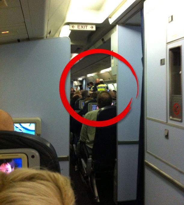 Matkustajan ottamassa kuvassa näkyy, kuinka häirikköä poistetaan koneesta.