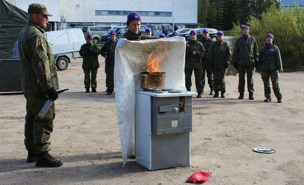 Petri Åberg opettaa Sirkku Kokkolalle rasvapalon sammuttamista.