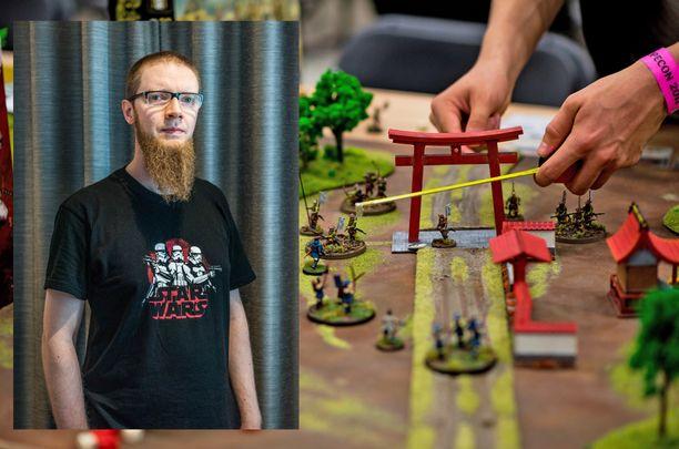 Mika Joensuu on löytänyt keinon yhdistää työnsä ja oman kiinnostuksen kohteensa. Taustalla näkyvässä kuvassa on meneillään Test Of Honor -miniatyyripeli, jonka miniatyyrien ja maastojen valmistamisesta ovat vastanneet Figure Fellows ry:n jäsenet.