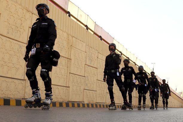 Mustiin pukeutuneet rullaluistinpoliisit partioivat krikettistadionin ulkopuolella Karachissa.