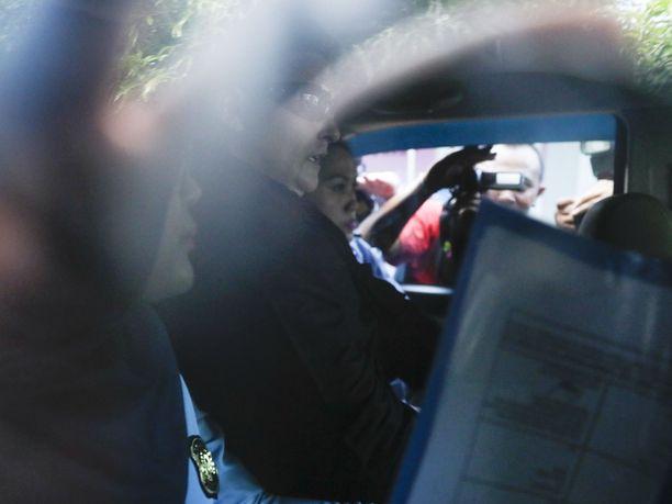 Renae Lawrence istui (keskellä aurinkolaseissa) maahanmuuttoviranomaisten autossa vapauduttuaan.