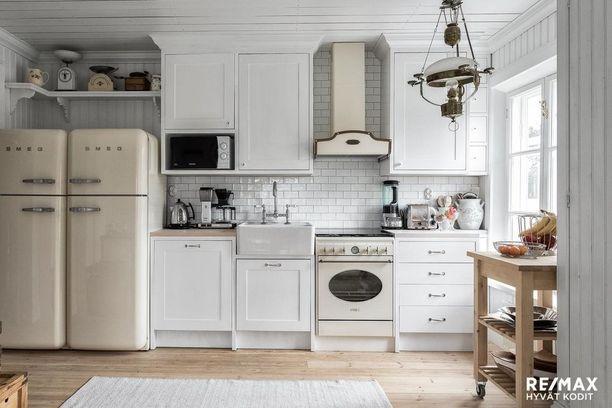 Vanhanaikaiseksi muotoillut uudet kodinkoneet kruunaavat tämän keittiön maalaisromanttisen tyylin. Tunnelmaan sopivat loistavasti myös vanha lamppu ja hyllyllä olevat vanhat esineet.