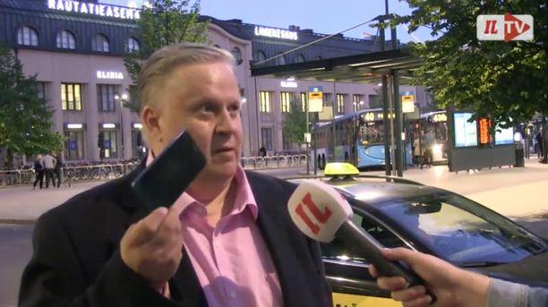 Timo Liespuu nostaa kännykkäänsä näyttääkseen, mitä tarvikkeita tarvitsee Uber-taksipalveluiden ajamiseen.