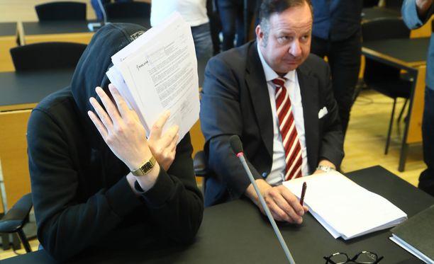 Michael Penttilä peitti kasvonsa papereilla tiistaiaamuna oikeudenkäynnin alkaessa. Aiemmin hän on ollut esillä kasvoillaan, usein aurinkolasit päässään tosin.