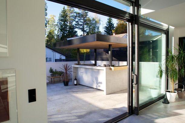 Tämä betoninen kesäkeittiö sijaitsee kivitalon terassilla. Jykevä katos suojaa ruoanlaittoa sateisellakin säällä.