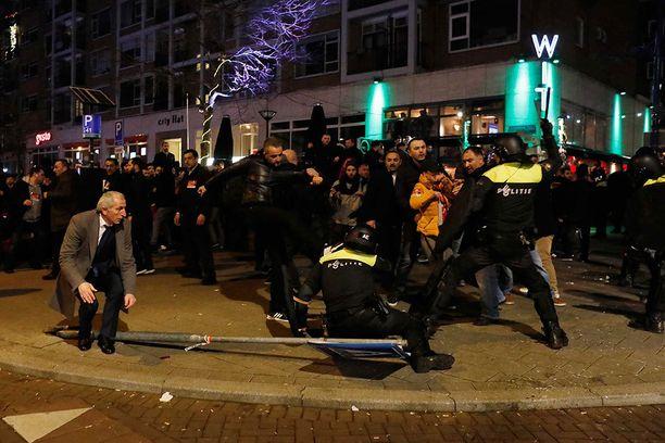 Mielenosoitukset Rotterdamissa muuttuivat nopeasti väkivaltaisiksi. Kuvassa yksi mielenosoittaja yrittää potkaista maassa olevaa mellakkapoliisia.