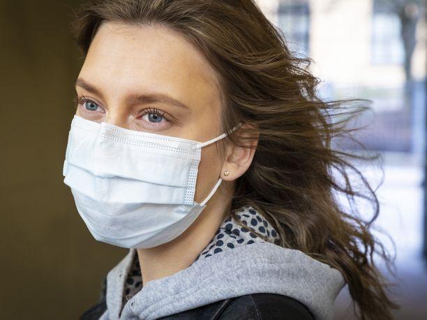 Nuori suomalainen nainen käyttää hengityssuojainta. Kuvituskuva.