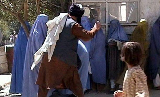 Uskonnollinen poliisi hakkaa naista Kabulissa vuonna 2001. Talibanin alaisuudessa maassa noudatettiin islamilaista lakia.
