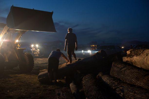 STANDING ROCK Nykyajan ongelmat -reportaasisarjan voittajaotokset vievät Sioux-heimo Standing Rockin maille, jossa Dakota Access -öljyputken rakentaminen uhkaa heidän maitaan. Vastamielenosoittajien leirissä päivittäiset tehtävät kuten polttopuiden teko ja ruoanlaitto ovat etulinjaa. Kuvassa miehet purkavat polttopuulastia. Heillä oli vastassaan mellakkapoliisin sotilasajoneuvoja, kyynelkaasua, vesitykkejä ja kumiluoteja.
