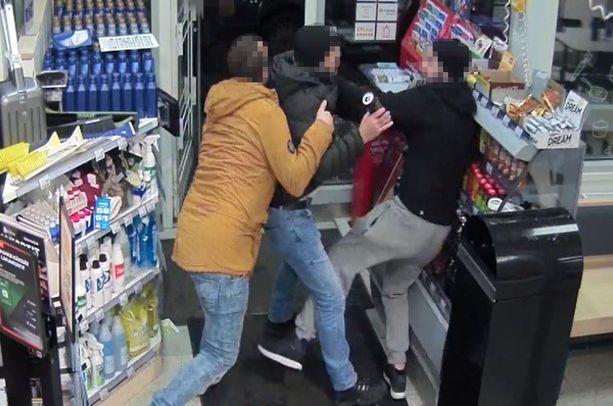 Kampin ampujan (vas.) päälle käytiin huoltoasemalla. Mies kävi lyöjän (oik.) päälle niin, että juomakaappi siirtyi paikaltaan. Keskellä oleva ampujan tuttava pyrki estämään nyrkkitappelun.
