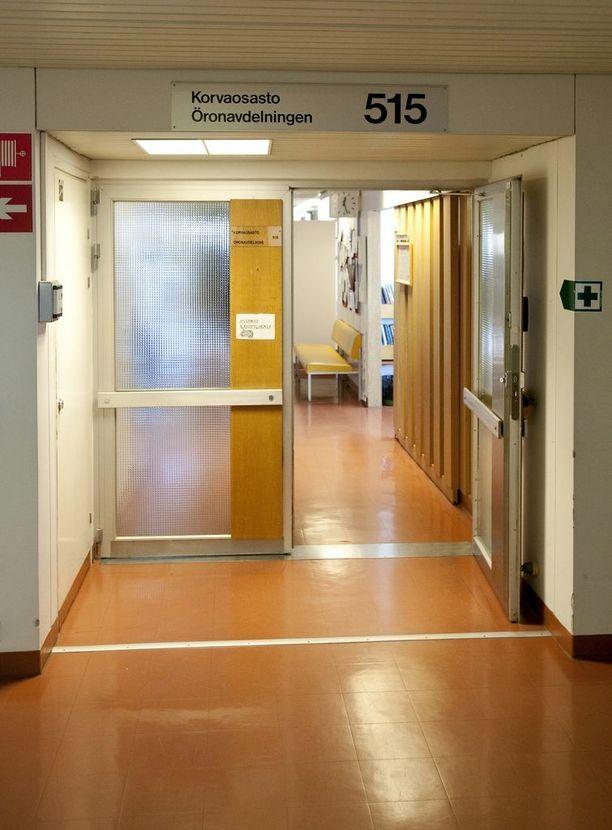 Sairaalan vartijat taltuttivat kaasusumuttimen avulla syytetyn naisen osaston väliovelta. Kuvituskuva eräästä Tyksin ovesta.