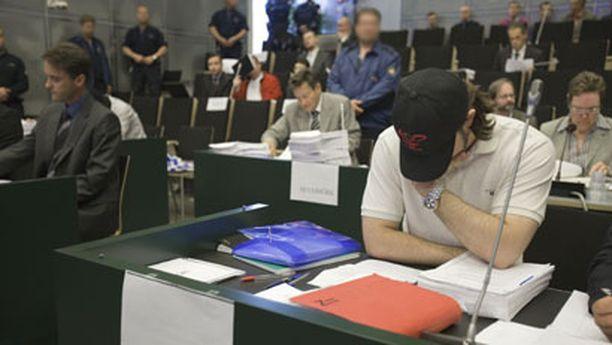 Raharyöstöistä syytetyt peittivät kasvonsa oikeudenkäynnin alussa.