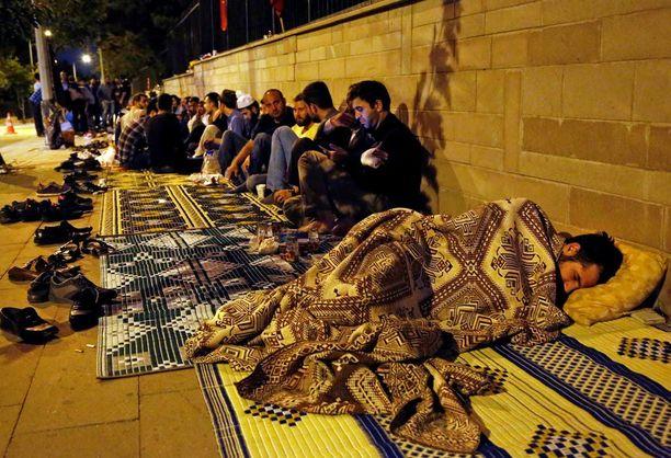 """Hallitusta tukevat mielenosoittajat istuivat myöhään tiistai-iltana pääministerin toimiston edustalla Ankarassa. He kutsuvat itseään """"Demokratian puolustajiksi""""."""