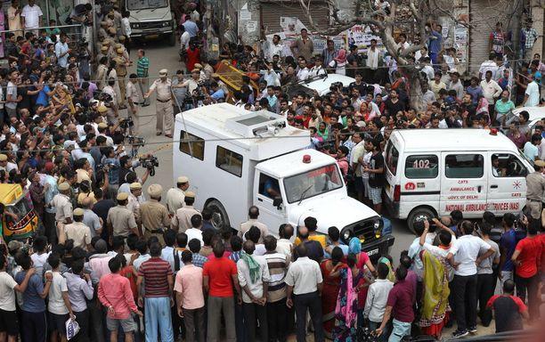 Ambulanssit kuljettivat perheenjäsenten ruumiit pois Delhissä.