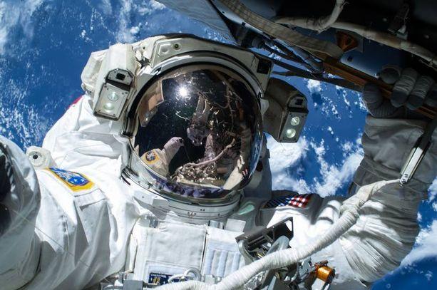 Barry Wilmore poseerasi maapallon edessä, Terry Virts heijastuu visiiristä.