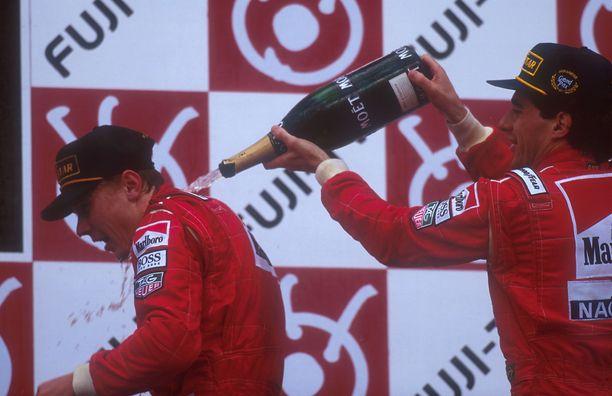 Kisan voittanut Ayrton Senna kaatoi samppanjaa Mika Häkkisen niskaan Japanin osakilpailun palkintopallilla lokakuussa 1993.