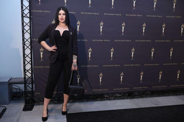 Kielinaisena ja artistina tunnettu SAARA oli valinnut ylleen graafisen haalarin ja mustan jakun. Tyylin täydensi Chanelin käsilaukku ja musta polkkatukka.