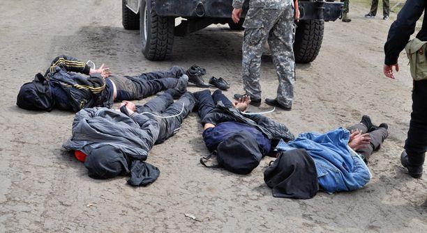 Ukrainan puolustusministeriön luovuttamassa kuvassa on neljä miestä, joiden epäillään ampuneen armeijan helikopterin alas.